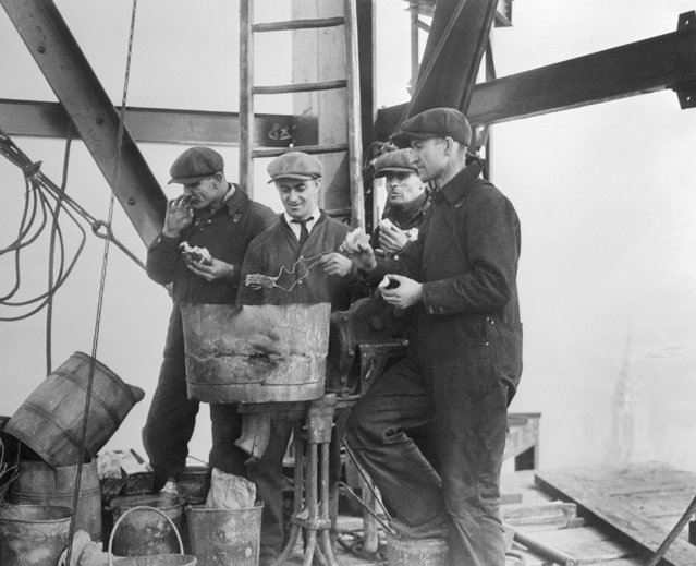 Noon hour on the top of the mooring mast and tower of the gigantic Empire State Building, rising on the site of the old Waldorf on November 05, 1930. Men toasting their bread and heating coffee on the rivet heater, high above all other man made structures in New York – just reaching 100 stories. (Photo by Bettmann/Getty Images)