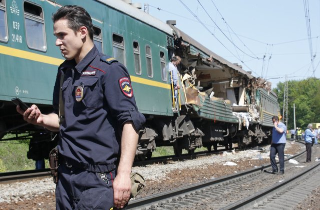 An Interior Ministry security force member stands guard near a passenger train damaged in a collision with a freight train in Moscow region May 20, 2014. The passenger train on its way to Moldova collided with a freight train near Moscow on Tuesday, killing at least four people and injuring 15, a spokeswoman for Russia's Emergencies Ministry said. The reason for the collision, near the town of Naro-Fominsk 55 km (34 miles) southwest of Moscow, was not immediately clear. (Photo by Grigory Dukor/Reuters)