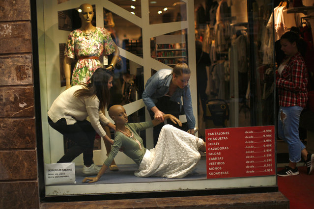 Workers move a mannequin in a women's clothing shop in downtown Malaga, southern Spain, April 1, 2016. (Photo by Jon Nazca/Reuters)