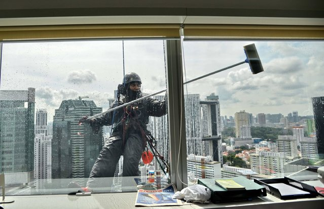 A worker dangling from safety ropes, cleans windows of a high-rise office building in the business district of Singapore on May 11, 2017. (Photo by Toh Ting Wei/AFP Photo)