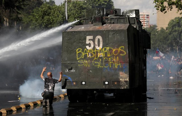 """Demonstrators are sprayed by riot police with a water cannon during an anti-government protests in Santiago, Chile on October 28, 2019. The graffiti on the riot police vehicle reads: """"Unglorious bastards"""". (Photo by Edgard Garrido/Reuters)"""