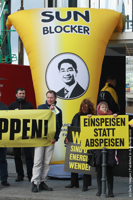 Activists protesting cuts in subsidies to solar power in Germany protest outside the building where Vice Chancellor and Economy Minister Philipp Roesler and Environment Minister Norbert Roettgen were announcing the cuts