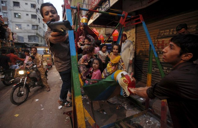 A boy (L) gestures with a toy gun while children play on a swing along a street during Eid al-Fitr, which marks the end of the holy month of Ramadan, in Karachi, Pakistan, July 20, 2015. (Photo by Akhtar Soomro/Reuters)