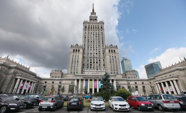 In this photo taken Monday, July 20, 2015, cars are parked in front of the Palace of Culture and Science in  Warsaw, Poland. The building was a gift from Soviet leader Josef Stalin and is celebrating its 60th birthday on Wednesday. Some officials called for the building to be torn down in a symbolic gesture after Poland shed communism and Moscow's dominance in 1989, but the opinion prevailed that it is a witness to national history and should be preserved. (Photo by Czarek Sokolowski/AP Photo)