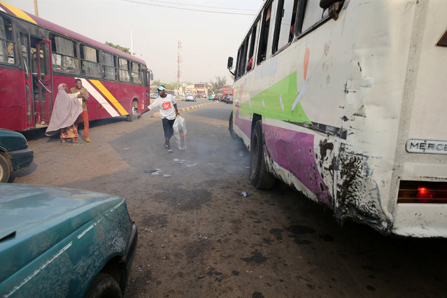 A man walks towards a bus discharging fumes from its exhaust at a bus park in Abuja, Nigeria, February 1, 2017. (Photo by Afolabi Sotunde/Reuters)