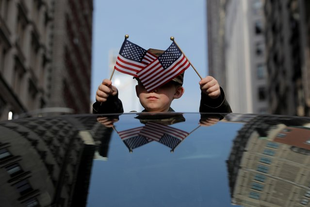 Liam Ross, 6 from Virginia, waves U.S. flags from the top of a car in the Veterans Day Parade in Manhattan, New York City, U.S., November 11, 2019. (Photo by Andrew Kelly/Reuters)