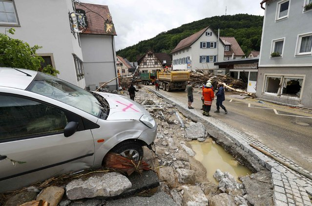 A damaged car lies amongst debris following floods in the town of Braunsbach, in Baden-Wuerttemberg, Germany, May 30, 2016. (Photo by Kai Pfaffenbach/Reuters)