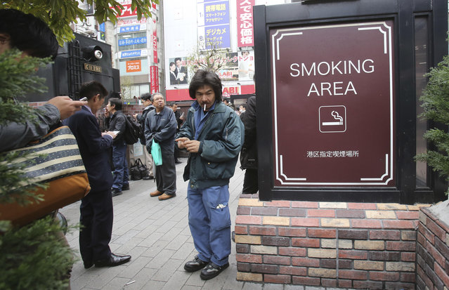 People gather at the smoking area in Tokyo, Friday, April 7, 2017.  The senior World Health Organization official says Japan should go fully smoke-free in public places if it wants success in Tokyo Olympics and tourism promotion. (Photo by Koji Sasahara/AP Photo)