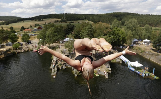 A participant jumps before diving into the water during a high jump competition near the village of Hrimezdice, Czech Republic, Friday, July 31, 2015. (Photo by Petr David Josek/AP Photo)