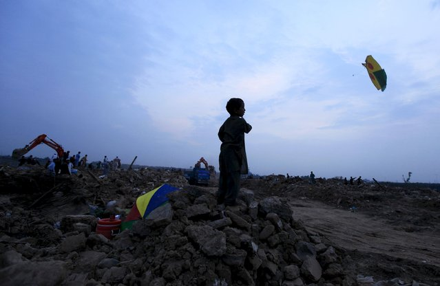 A boy flies a kite at the debris of his family's house as a excavator destroys his neighborhood at a slum on the outskirts of Islamabad July 31, 2015. According to local media, the Capital Development Authority (CDA) has started to demolish illegal settlements on the outskirts of Islamabad where Afghan refugees and people from Pakistan's tribal area have escaped from the military operations. (Photo by Faisal Mahmood/Reuters)