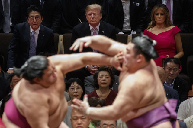 President Donald Trump attends the Tokyo Grand Sumo Tournament with Japanese Prime Minister Shinzo Abe at Ryogoku Kokugikan Stadium, Sunday, May 26, 2019, in Tokyo. First lady Melania Trump is at top right. (Photo by Evan Vucci/AP Photo)