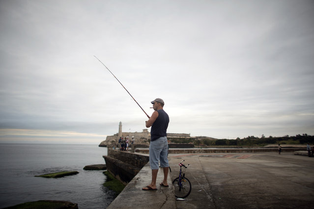 """Pastor Silva, 47, a railway system employee, fishes during his free time at the seafront boulevard """"El Malecon"""" in Havana, December 20, 2014. (Photo by Alexandre Meneghini/Reuters)"""