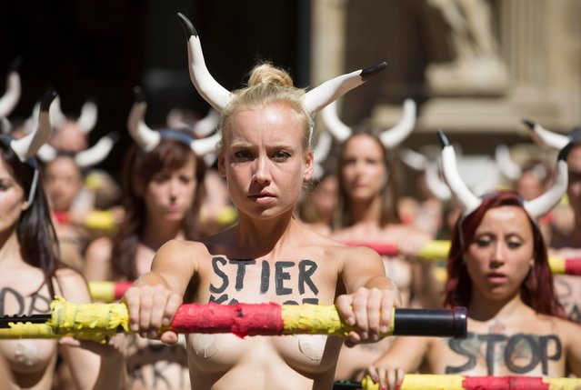 "Topless protesters from the organization PETA (People for the Ethical Treatment of Animals) stand with ""banderillas"" filled with red powder as about 100 people rally in front of the town hall square in Pamplona, Navarra, northern Spain, demonstrating against the treatment of fighting bulls in the Fiesta de San Fermin, 05 July 2017. The renowned eight-day festival made famous by Ernest Hemingway's 1926 novel ""The Sun Also Rises"" has running-with-the-bulls and a bullfight each day for the fair, which begins at noon on 06 July 2017. (Photo by Jim Hollander/EPA)"