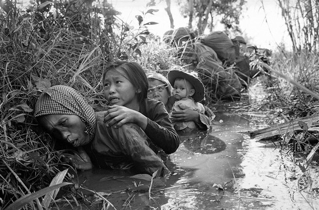 In this Jan. 1, 1966 photo, women and children crouch in a muddy canal as they take cover from intense Viet Cong fire at Bao Trai, about 20 miles west of Saigon, Vietnam