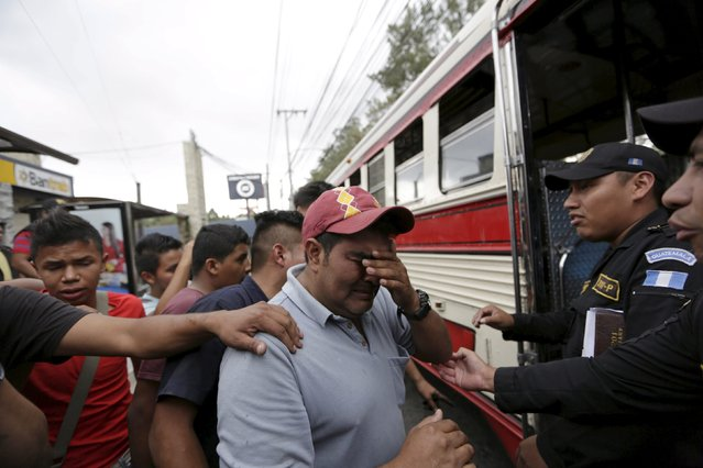 A man reacts at a crime scene, where the driver of a public bus and his assistant were shot dead, in Mixco, on the outskirts of Guatemala City, August 11, 2015. Four people died in three armed attacks on buses in the cities of Guatemala and Mixco, local media reported on Tuesday, adding that the murders were related to cases in which the drivers refused to pay extortion to criminal gangs. (Photo by Jorge Dan Lopez/Reuters)
