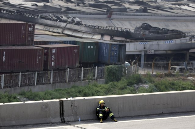A firefighter rests on a highway next to the site of explosions at the Binhai new district in Tianjin August 13, 2015. (Photo by Jason Lee/Reuters)