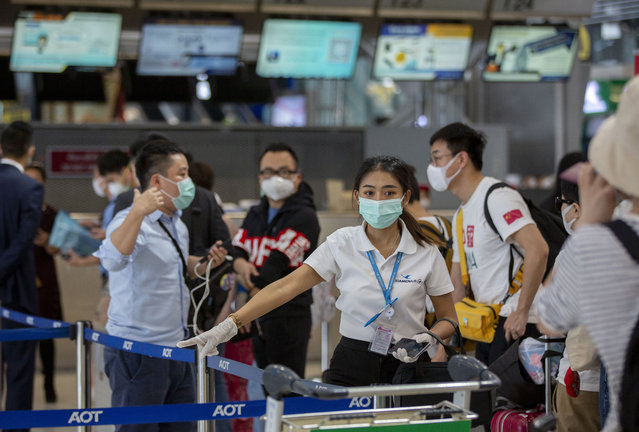 An airline staffer assists tourists from Wuhan, china, as they wait for a charter flight back to Wuhan at the Suvarnabhumi airport, Bangkok, Thailand, Friday, January 31, 2020. A group of Chinese tourists who have been trapped in Thailand since Wuhan was locked down due to an outbreak of new virus returned to China on Friday. (Photo by Gemunu Amarasinghe/AP Photo)