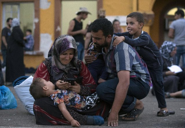 A migrant family shares a moment as they wait for a train to arrive at Gevgelija train station in Macedonia, close to the border with Greece, August 14, 2015. (Photo by Stoyan Nenov/Reuters)