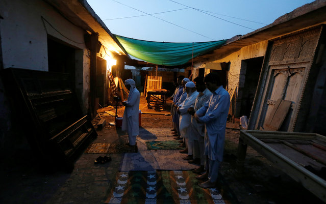 Workers and neighbours of a carpentry workshop pray after breaking their fast during the holy month of Ramadan in Islamabad, Pakistan June 11, 2016. (Photo by Caren Firouz/Reuters)
