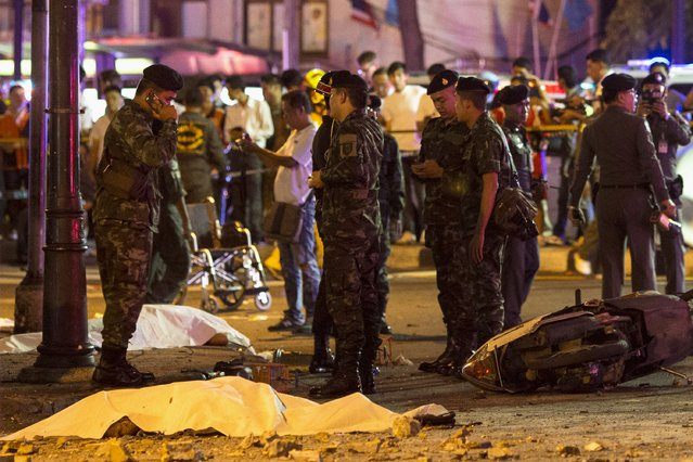 Bodies of victims are covered with white sheet as security forces and emergency workers gather at the scene of the blast in central Bangkok August 17, 2015. (Photo by Athit Perawongmetha/Reuters)