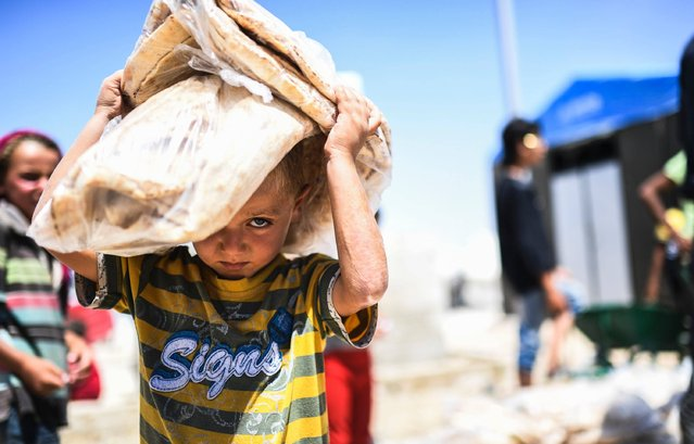 A displaced Syrian child who fled the countryside surrounding the Islamic State (IS) group's Syrian stronghold of Raqa, carries bread at a temporary camp in the village of Ain Issa on July 11, 2017. (Photo by Bulent Kilic/AFP Photo)