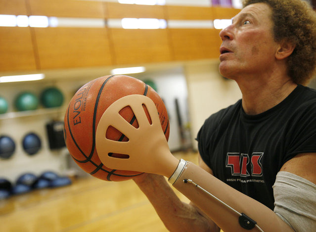Bob Radocy of TRS Inc. holds a basketball with a prosthetic hand designed for the sport at a gym in Boulder, Colorado August 21, 2009. Radocy designs and builds prosthetic attachments that allow amputee athletes to participate in multiple sports. (Photo by Rick Wilking/Reuters)