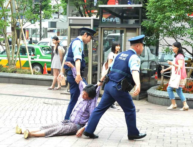 Police drag a drunk man to the koban in Shibuya, Japan on July 21, 2012. (Photo by Mark Buckton)