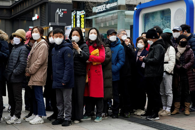 People wearing masks after the coronavirus outbreak wait in a line to buy masks in front of a department store in Seoul, South Korea, February 28, 2020. (Photo by Kim Hong-Ji/Reuters)
