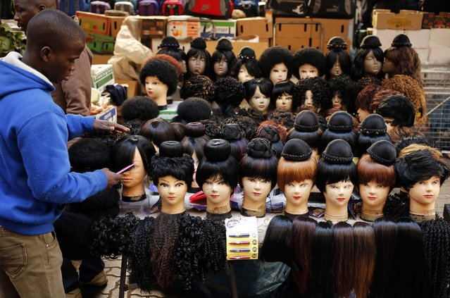 Man prepares wigs as he waits for customers in downtown Johannesburg. Some estimates put Africa's dry hair industry at as much as $6 billion a year; Nigerian singer Muma Gee recently boasted that she spends 500,000 naira ($3,100) on a single hair piece made of 11 sets of human hair. (Photo by Siphiwe Sibeko/Reuters)