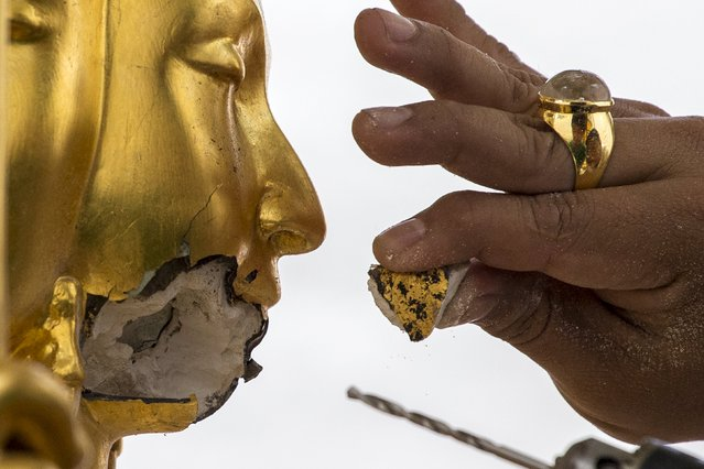 A craftsman fixes the statue of Hindu god Brahma after it was damaged during the deadly blast at the Erawan shrine in Bangkok, Thailand, August 26, 2015. Police on Tuesday questioned a taxi driver who may have driven the main suspect away from the area of last week's deadly attack in Bangkok, as forensic experts struggle to unearth vital evidence in Thailand's worst ever bombing. (Photo by Athit Perawongmetha/Reuters)