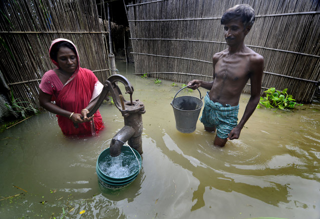 A wife and husband collect drinking water from a well source which is half submerged by flood water in the flood affected Morigaon district of Assam state, India, August 18, 2014. (Photo by EPA/STR)