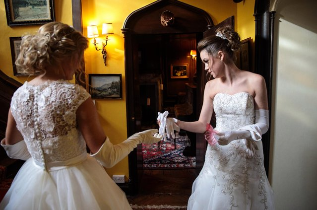 Debutante Olivia Mott, 20, from Charlottesville, Virginia (L) passes Callan Foran (R), 20, from Ohio a pair of white gloves as they prepare at Boughton Monchelsea Place ahead of the Queen Charlotte's Ball on September 9, 2017 in Maidstone, England. (Photo by Jack Taylor/Getty Images)