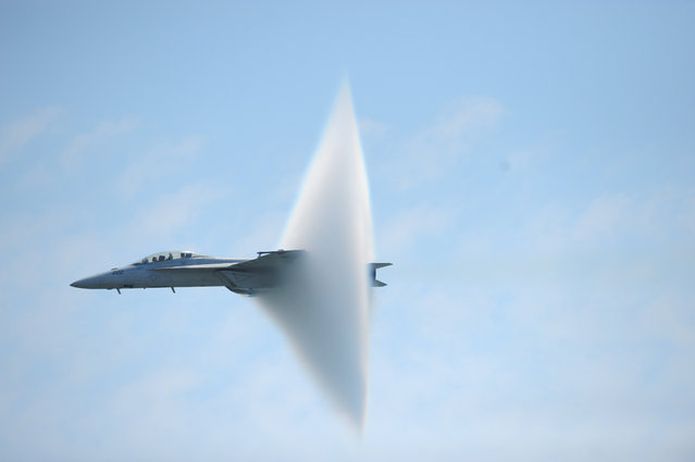 A ring of water vapor is created as pilots Lt. Justin Halligan (L) and Lt. Michael Witt (R) fly their F/A-18F Super Hornet airplane within 200mph of breaking the sound barrier while performing at New York Air Show at Jones Beach in Wantagh, New York, May 23, 2009. (Photo by Christopher Pasatieri/Reuters)