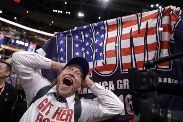 California delegate Jake Byrd reacts as New York delegate Bob Hayssen holds up a Trump flag during the second day session of the Republican National Convention in Cleveland, Tuesday, July 19, 2016. (Photo by John Locher/AP Photo)