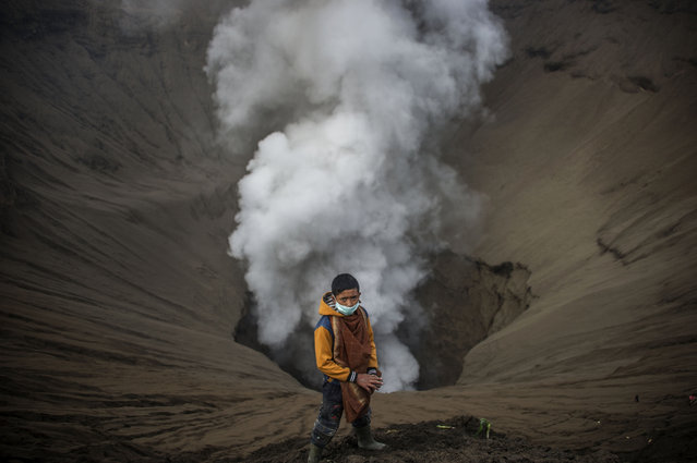 An Indonesian boy waits as he prepares to catch offerings released by Hindu devotees of the Tengger tribe during the Yadnya Kasada festival, on the crater of Mount Bromo in Probolinggo on July 21, 2016. During the annual Yadnya Kasada festival the Tenggerese climb Mount Bromo, an active volcano, and seek the blessing from the main deity Hyang Widi Wasa by presenting offerings of rice, fruit, livestock and other local produce. (Photo by Juni Kriswanto/AFP Photo)
