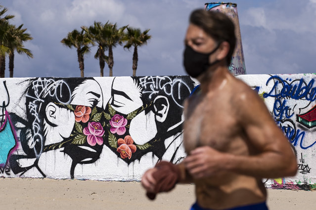 A man wearing a face mask jogs past a mural showing a couple kissing with face masks next to the beach amid the coronavirus pandemic in Venice, California, USA, 28 March 2020. Los Angeles Mayor Eric Garcetti ordered yesterday for all the beaches and trails to be closed to fight against the spread of the epidemic. (Photo by Etienne Laurent/EPA/EFE)