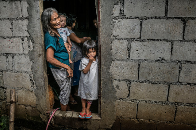 Remy Fernandez, 84, holds her grandchild, RJ, in the front door of her cinder block house, built beside a huge rubbish dump in Payatas, in Metro Manila. She is raising seven grandchildren because her son, Constantino de Juan, a drug user, was killed by masked men. The mother of the children is in prison on drugs charges. RJ was born in prison. Masked assassins entered the house through this front door and shot her son. Police deny claims by rights groups that the vigilantes who carry out many such killings are paid by them. (Photo by James Whitlow Delano/Funded by the Pulitzer Center on Crisis Reporting/The Guardian)