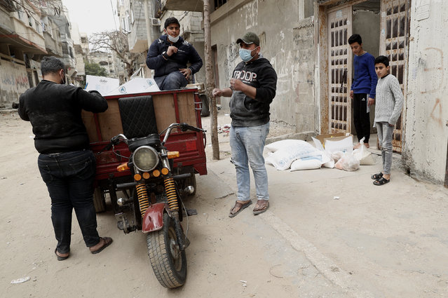 Palestinian workers distribute food supplies from the United Nations Relief and Works Agency (UNRWA) to a house, in the Sheikh Redwan neighborhood of Gaza City, Tuesday, March 31, 2020. The UN has resumed food deliveries to thousands of impoverished families in the Gaza Strip after a three-week delay caused by fears of the coronavirus. (Photo by Adel Hana/AP Photo)