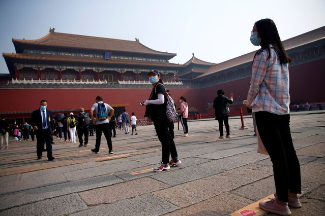 Visitors wearing face masks practice social distancing as they line up to enter the Forbidden City before its reopening on the first day of the five-day Labour Day holiday following the coronavirus disease (COVID-19) outbreak, in Beijing, China on May 1, 2020. (Photo by Tingshu Wang/Reuters)