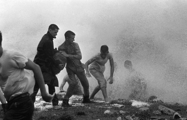 A group of volunteer's passes sandbags and duck sea spray in an effort to save a seawall at Jacksonville Beach on September 9, 1964 as the heavy seas and wind eat at the shore line. High seas have lashed the Florida coast and caused heavy damage to homes and power lines. (Photo by AP Photo)