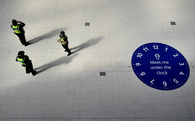 Police officers are seen in Waterloo station during the morning rush hour following the outbreak of the coronavirus disease (COVID-19), London, Britain, May 19, 2020. (Photo by Toby Melville/Reuters)
