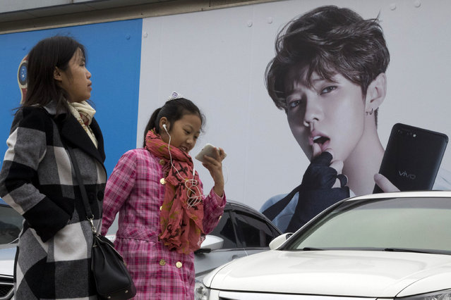 In this Saturday, October 21, 2017 photo, Chinese women walk past advertisement featuring teen idol Lu Han, also known as China's Justin Bieber in Beijing, China. China works to stifle celebrities as it seeks to dictate the values the nation's youth should embrace. It's part of the most ambitious effort in years to shape the country's booming entertainment industry. Instead of selfish, rich stars, the state is promoting performers who are all about patriotism, purity and other values that support the party's legitimacy, whether in movies about revolutionary heroes or through rap music. (Photo by Ng Han Guan/AP Photo)