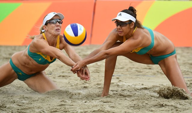 Australia's Louise Bawden (L) and Australia's Taliqua Clancy vie for the ball during the women's beach volleyball qualifying match between the Netherlands and Australia at the Beach Volley Arena in Rio de Janeiro on August 10, 2016, for the Rio 2016 Olympic Games. (Photo by Leon Neal/AFP Photo)
