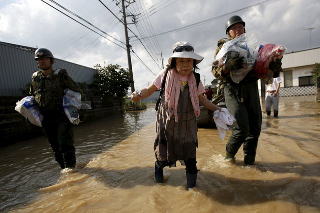 Local resident Yoshiko Nakamura (C), 66 years old, is escorted by Japanese Self-Defence Force's 1st Infantry Regiment soldiers as she is helped to leave from her home at a residential area flooded by the Kinugawa river, caused by Typhoon Etau in Joso, Ibaraki prefecture, Japan, September 12, 2015. (Photo by Issei Kato/Reuters)