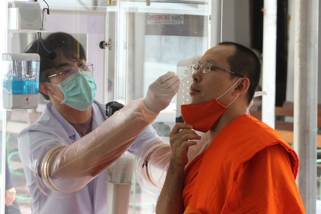 Health workers collect a nasal swab sample from a Buddhist monk to test for the coronavirus at the Wat Pho temple in Bangkok, Thailand, Saturday, May 30, 2020. (Photo by Sarayuth Jojaiharn/AP Photo)