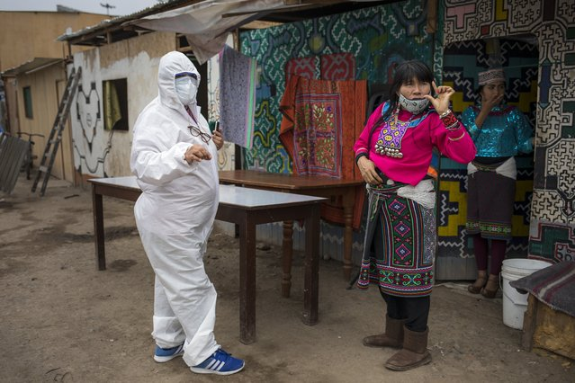 Olinda Silvano from the Shipibo Conibo ethnic group, talks to a member of an NGO dressed in protective gear against the new coronavirus, during the celebration of the feast of Saint John the Baptist, the patron saint of the Peruvian Amazon, in the Cantagallo neighborhood of Lima, Peru, Wednesday, June 24, 2020. The neighborhood reopened about 10 days ago after it had been under strict quarantine due to an outbreak of COVID-19. (Photo by Rodrigo Abd/AP Photo)