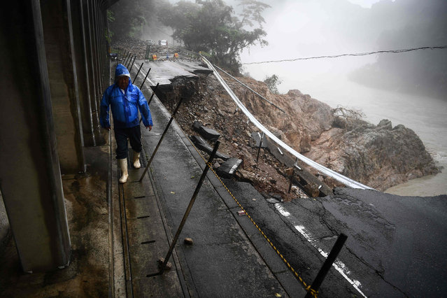 """A man walks by a collapsed road caused by heavy rain in Kuma, Kumamoto prefecture on July 7, 2020. Emergency services in western Japan were """"racing against time"""" to rescue people stranded by devastating floods and landslides, with at least 50 feared dead and more torrential rain forecast. (Photo by Charly Triballeau/AFP Photo)"""