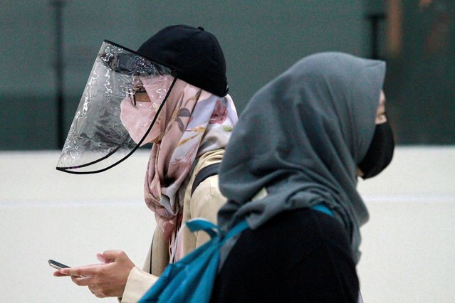 Women are pictured wearing a protective face mask and face shield as the Indonesian government eases restrictions to prevent the spread of the coronavirus disease (COVID-19) outbreak in Jakarta, Indonesia, June 8, 2020. (Photo by Ajeng Dinar Ulfiana/Reuters)