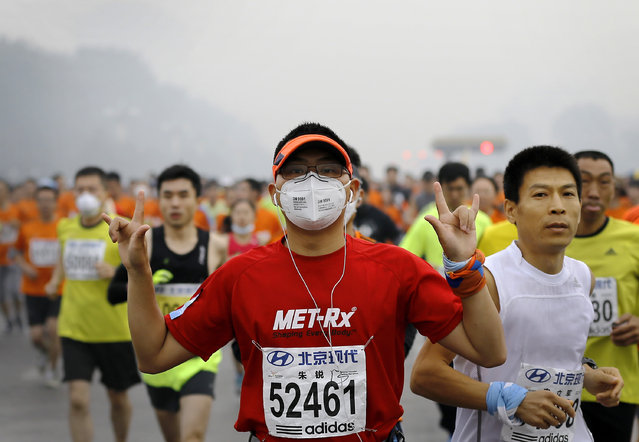A runner wearing a mask to protect himself from pollutants gestures as he and others jog past Chang'an Avenue near Tiananmen Square shrouded in haze at the start of 2014 Beijing International Marathon in Beijing, China Sunday, October 19, 2014. (Photo by Andy Wong/AP Photo)