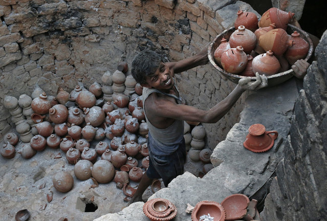 A potter carries a basket filled with clay money boxes at a workshop ahead of the Hindu festival of Diwali in New Delhi October 16, 2014. (Photo by Anindito Mukherjee/Reuters)